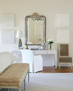 Chic French bedroom features a white makeup vanity and desk paired with a white slipcovered chair placed under a distressed silver mirror flanked by white abstract canvas art.