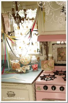 Victorian trailer...all decked out with tin ceiling, Victorian cabinet pulls, pink stove, gingerbread and more; cute!