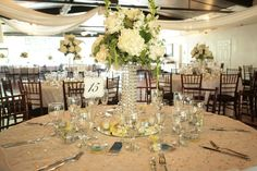Tall white centerpieces on a sparkle linen with a touch of yellow in the petals below and ribbon around the gift boxes. Gorgeous! #weddingideas