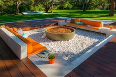 Gather around the fire pit for intimate conversation in this built in seating area. The pop of orange is repeated in the fire pit and various accents around the space.