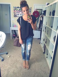 Distressed pair of jeans with a loose black top and a messy bun for a perfect casual look