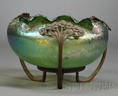 Bohemian Glass Bowl   Art glass and bronze   20th century   Bowl with pinched rim on green iridescent body with polished pontil held by stylized floral bronze mounts joined to circular base, dia. 8, ht. 5 1/2 in.