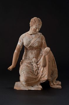 "This figurine depicts a young woman crouching to play knucklebones,a popular Greek game similar to modern-day ""jacks"".She is dressed in a thin chito (a long tunic commonly worn in ancient Greece)pinned over one shoulder, a separate loose shawl tied around her hips.Her hair is parted and twisted in a simple melon-coiffure knot decorated with ribbons.Her kneeling stance suggests she is actively engaged in play,and her right arm is drawn back as if about to toss the knucklebones or ""astragaloi"""