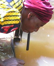 Nigerian woman using pipe filter to drink water directly from pond