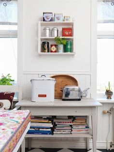 A tiny table nestled at the end of the kitchen with lots of cook books and a cute little cubby. Wish I could do that in our kitchen.