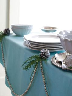 The buffet table is adorned with a silver beaded garland and greens punctuated by pine cones. Use safety pins to hold the garland in place.