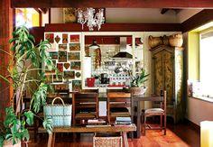 A sala de jantar com pé-direito duplo fica ao lado da cozinha, revestida de cerâmica talavera. A parede à esquerda do passa-pratos foi decorada com ex-votos mexicanos. Mesa é de baraúna. Armário comprado em Bichinho e banco em Tiradentes, cidades mineiras