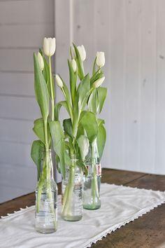 Spring centerpiece on a farmhouse kitchen island. Glass soda bottles and white tulips. Kitchen Island Centerpiece, Farmhouse Outdoor Decor, Plant Centerpieces, Farmhouse Kitchen Island, Green Paint Colors, White Tulips, Faux Plants, Cottage Style, Farmhouse Style