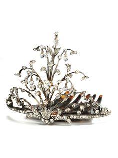 Breakfast at Tiffany's - This tiara is characteristic of Edwardian period.  Designed in the favored naturalistic form of a floral spray, silver topped gold unites with white pastes to create a tiara, hinged onto a comb of natural tortoise shell.  Rising high, sprays of botanical profiles and outlines are set with clear white pastes and are punctuated with seven briolette paste dangles.