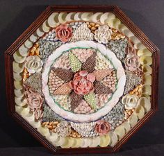 "Sailor's valentine with a center star shape design with colorful rosettes in an enclosed octagon case.  English c. 1890.  Size:  13"" H x 13"" W http://www.leatherwoodantiques.com/images/NauticalArt/NA-0059.jpg"