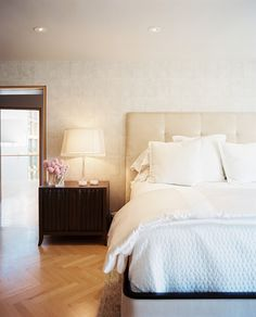 Contemporary Bedroom - A wooden bedside table and a tufted headboard atop herringbone-patterned hardwood flooring