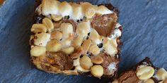 Fantastisk simpel opskrift på den lækreste brownie med Rocky Road. Den intense kage spiller perfekt sammen med karamellerne, de bløde skumfiduser og ristede peanuts.