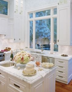 White cabinets, white marble counter tops, and white stone tile backsplash in a traditional kitchen — Danenberg Design — Featured in Gentry Magazine & CalFinder