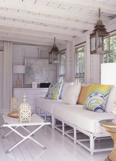 Chic Cottage Living Room  Carved lanterns, Pucci-style printed pillows and seashells add pattern and texture to an all-white space.