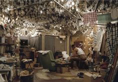 In another of Jeff Wall's photo, we see a black man with his back facing the camera. He is in a brightly illuminated room with the ceiling full of light-bulbs. The room is cluttered and chaotic, and he is engrossed in his work. The art-piece exposes the black man's private world, such that the viewer cannot ignore his presence, his strength, or his poverty.