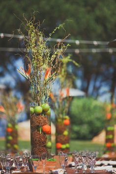 orange, green and brown tall vases with balls of twine and fruit. #wedding reception centerpieces.