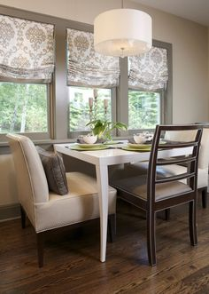 The Milo Made 2 Measure dining table in the breakfast nook is a pair of Bistro Banquettes in Vacona Downy Gray. The Dara side chairs have a dark walnut finish with antique rub silver striping and elephant colored fabric. --Hickory Chair Furniture