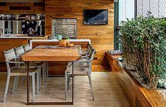 rea das refeições | Embutida no painel de madeira, churrasqueira a gás da Construflama. Mesa de jantar da Tora Brasil. Cadeiras Play, da Ded...