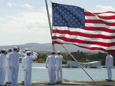 Sailors aboard the Nimitz-class aircraft carrier USS CARL VINSON (CVN 70) hoist colors alongside the USS Arizona Memorial as the ship moors at Pearl Harbor. USN photo.