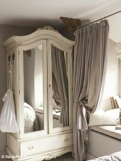 Armoire and curtain around bed
