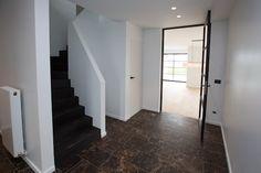 Smeedijzeren deur en zwart deurbeslag gaan hand in hand met marmeren vloertegel en zwart gebeitste trap.