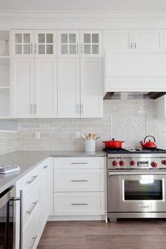 Pops of red bring life to this gorgeous white and gray kitchen featuring a Wolf range topped with a red kettle and pot positioned in front of a wall covered in light gray mini subway tiles framing diamond pattern cooktop tiles fixed beneath a white kitchen hood flanked by white shaker cabinets with nickel pulls positioned under glass front display cabinets.