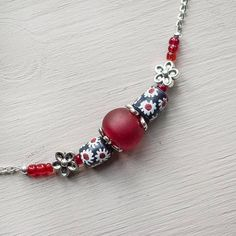 Dainty silver necklace with cute recycled glass beads from Ghana, hand made by Challey Ayekoo. She loves me, she loves me not..... The daisy, long a symbol of innocence, purity and true love is teamed here with a fiery red recycled glass bead to remind us that we all have a not so
