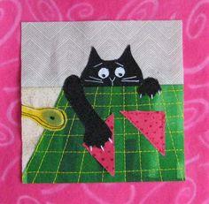 cat stealing fabric off the cutting mat.