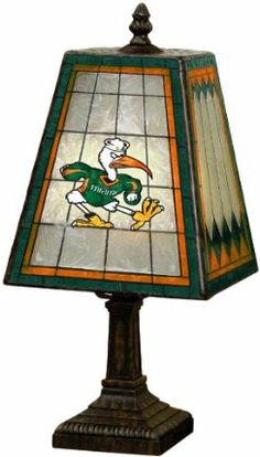 "NCAA Miami 14"" Art Glass Table Lamp by The Memory Company. $49.99. Takes a 40 Watt G16.5 style Bulb. Bulb not included. 14.5tall by 7 3/8 wide. Made of Hand-Painted Art Glass. Team logos on two sides. NCAA Miami 14"" Art Glass Table Lamp"