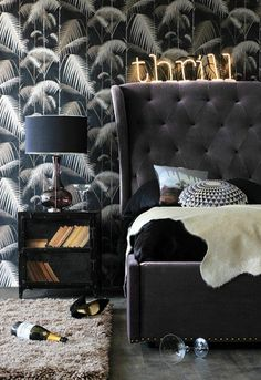 chambre à coucher sombre en noire et gris, tête de lit en velours, papier peint feuille de palmier sur fond noir