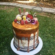 Chocolate mud cake with semi nude buttercream frosting, caramel drip, chocolates, berries and flowers.