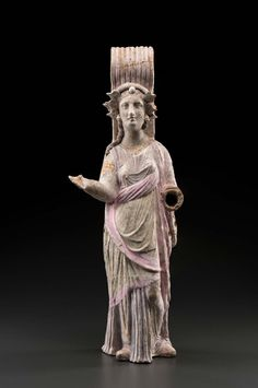 """Standing figure, broad striated strap handle rising up behind head, curving over to back of shoulders. spiraliform diadem, round central ornament, """"petals"""" at sides of face; tress over right shoulder. White slip remains of polychrome: gold necklace and armlets. lavender, pink and white draped garments. Holes for attachments on left side, large square hole in back. Has been broken and restored; cracks visible in handle; left forearm missing; fingers on right hand missing."""