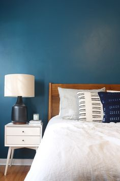 West Elm Mid-Century bed and nightstand, Excelsior poster, mud-cloth pillows, mid-century dresser, Benjamin Moore Galapagos Turquoise walls, dark teal bedroom
