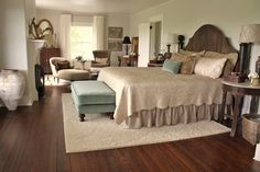 Shows the correct placement of a large area rug in the bedroom.  I've often wondered about that.  Love this room!