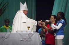 Cardinal Dolan receives gifts from women during Mass at World Youth Day in Brazil  New York Cardinal Timothy M. Dolan receives the gifts from two young women during a Mass at the Rio Vivo Welcome Center in Rio de Janeiro July 24. The site also will feature prayer and worship experiences, music, media and videos, motivational speakers, cultural presentations and networking activities for World Youth Day pilgrims. (CNS photo/Tyler Orsburn)