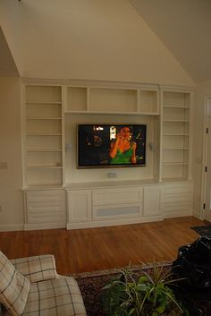 The TV is mounted to wall. Custom cabinets built surrounding TV to hide electronic components and base module. Storage pull-outs for cd's and dvd's.