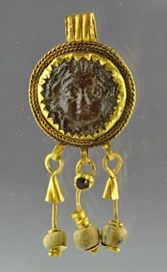 Roman gold pendant with glass token, 2nd centyry A.D. Roman gold jewelry with inserted glass token with Gorgon head, gold pendant with 3 gold chains with glass decorations, 1.9 cm diameter 4.8 cm long. Private collection