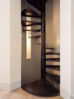 The landing of the metal spiral stair has been inscribed with precision into the wood floor.