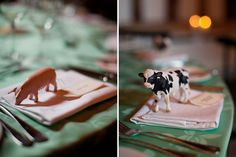 Figurines of farm animals hold down place cards at a wedding reception in a barn