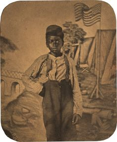 Studio portrait of African American boy with civil war encampment and American flag backdrop, 1864