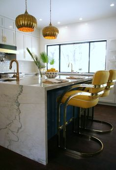 Love the waterfall edge countertop. Those retro cool stools in yellow/gold!