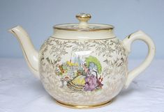 Beautiful teapot, made by Sadler England. It features the round Sadler shape and depicts a crinoline lady in her garden and a stunning gold chintz design. In good condition without cracks, but has a few signs of wear: theres a small chip under the tip of the sprout (see picture) and