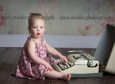 Sweet Two Year Old practices on her type writer for 2 year birthday pictures. Shea Studio Photography, Ackley Iowa
