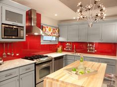 I like kitchens that have a sophisticated feel. So here they did rich gray on the cabinets but added color with a fuchsia-red glass backsplash that extends all the way up to the ceiling behind the range.