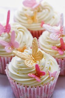 Butterfly Theme cupcakes.  could frost in white to match the cake and top with pink and purple fondant butterflies.