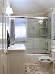 This traditional and beach-themed child's bathroom features dimensional pale gray subway tile, glass enclosed shower, white wood blinds, a small white vanity and black and white basketweave tile.
