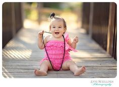 one year old pettiromper high heels necklace pearls necklace pink black outdoor portrait photo session birthday girl baby cake smash park lace studio picture  bridge shadow sunset golden hour https://www.facebook.com/anneschillingsphotography www.thehairbowcompany.com @TheHairBowCo