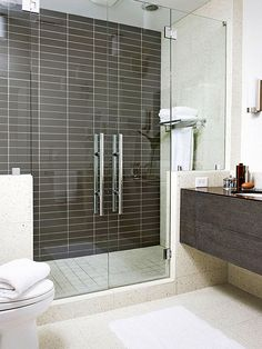 Coffee-color tiles cover this expanded shower's back wall, creating a high-contrast look with the rest of the room's creamy palette. A floating espresso vanity adds to the feeling of openness and offers much-needed storage! http://www.bhg.com/bathroom/remodeling/makeover/before-and-after-bathrooms/?socsrc=bhgpin122814highcontrastshower&page=6