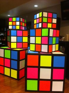 Rubik's cubes made from refrigerator boxes black primer paint spray adhesive and neon poster board from the .99 store.