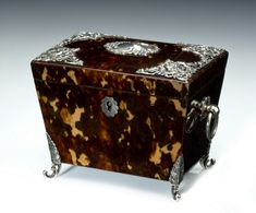 ANTIQUE TOROISESHELL AND SILVER TEA CADDY // An unusual small sarcophagus-shaped tortoiseshell tea caddy overlaid with silver mounts and central cartouche, silver ring handles to the sides and all raised on silver feet, the inside with a single tortoiseshell lidded compartment. - Height: 4.25 ins / 10.8 cms Width: 5.5 ins / 13.97 cms Depth: 3.5 ins / 8.89 cms //  Price: £3800 //  - Maria Elena Garcia -  ► www.pinterest.com/megardel/ ◀︎